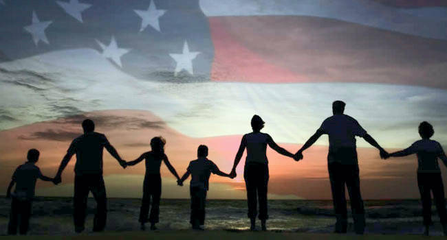 A group of people holding hands in front of an American flag